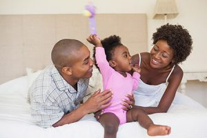 Happy parents and baby girl sitting on bed together at home in the bedroom